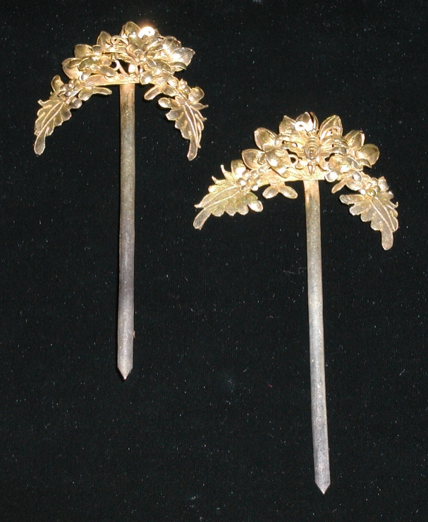 A pair of gilded hairpins.